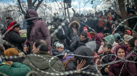 Des migrants sont assis derrière une clôture en fil de fer barbelé dans la zone tampon à la frontière turco-grecque à Pazarkule, dans le district d'Edirne, le 29 février 2020 (image d'illustration).