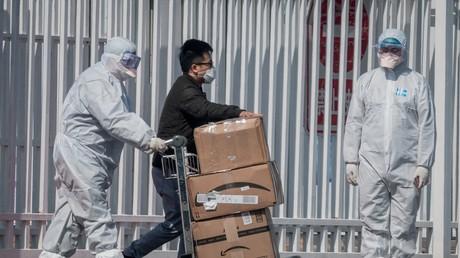 Des travailleurs portant des combinaisons de protection à titre préventif contre le coronavirus COVID-19 aident un passager à transporter ses affaires au New China International Exhibition Center, à Pékin, le 16 mars 2020 (image d'illustration).