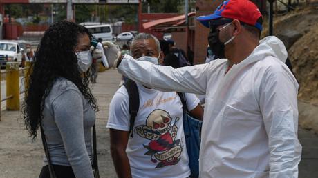 Un agent de santé vérifie la température d'une femme en dehors d'un marché municipal à titre de mesure préventive contre le nouveau coronavirus, COVID-19, à Caracas le 18 mars 2020.