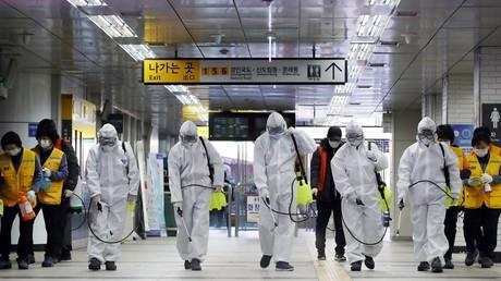Des travailleurs portant un équipement de protection désinfectent une station de métro à Séoul, le 11 mars 2020 (image d'illustration).