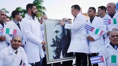 Des médecins cubains affichent un portrait de Fidel Castro lors d'une cérémonie avant de se rendre en Italie pour aider le pays européen contre le coronavirus (COVID-19), à La Havane, Cuba, le 21 mars 2020.