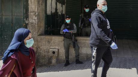 Les gardes-frontières israéliens regardent les Palestiniens passer, tous portant des masques de protection au milieu de l'épidémie de Covid-19, dans la vieille ville de Jérusalem, le 25 mars 2020.