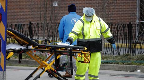 Un ambulancier pulvérise du désinfectant sur une civière à l'extérieur du Brooklyn Hospital Center pendant l'épidémie de Covid-19 dans le quartier de Brooklyn à New York, le 31 mars 2020.