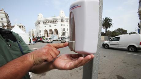 Un homme utilise un distributeur de désinfectant pour les mains dans la rue après la propagation de la maladie à coronavirus (COVID-19), à Alger (Algérie), le 21 mars 2020.