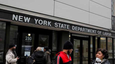 Des gens se rassemblent devant les bureaux du département du Travail, temporairement fermés au public en raison de l'épidémie de Covid-19 dans le quartier de Brooklyn (New York), le 26 mars 2020.