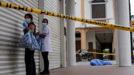 Des femmes se tiennent près du cadavre d'un homme qui s'était effondré sur le trottoir, lors de l'épidémie de coronavirus (Covid-19), à Guayaquil, Equateur, 30 mars 2020.