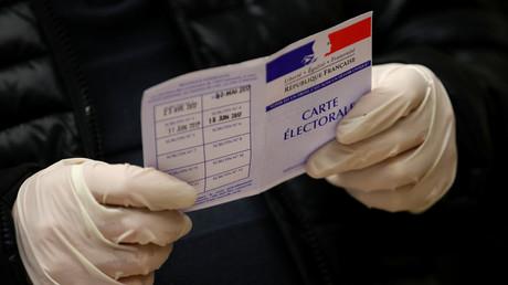 Un fonctionnaire, portant des gants en latex, tient une carte d'électeur dans un bureau de vote lors du premier tour des élections municipales à Strasbourg, le 15 mars 2020.