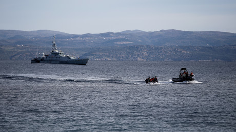 Un bateau de sauvetage escorte un canot avec des migrants en provenance d'Afghanistan alors qu'un navire Frontex patrouille en arrière-plan, sur l'île de Lesbos (Grèce) (image d'illustration).