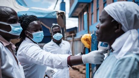 Des membres d'une ONG kenyane mesurent la température corporelle d'une femme dans le bidonville de Kibera à Nairobi, le 18 mars 2020.