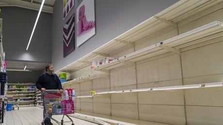 Un homme qui regarde des étagères vides d'un supermarché le 16 mars, à Pfastatt, dans l'est de la France (image d'illustration).