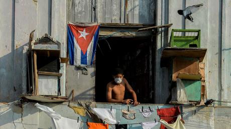 Un homme portant un masque de protection sur son balcon à La Havane