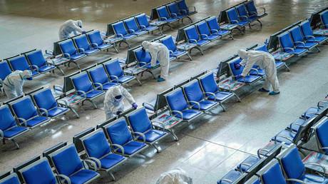 Des agents chinois en tenue de protection désinfectent les sièges du hall de la gare de Wuhan (Chine), en vue de sa réouverture prochaine (image d'illustration).