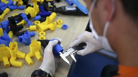 Le fondateur d'Icare entreprise française Jeremy Neyrou travaille sur des pièces réalisées à partir d'une imprimante 3D lors d'un atelier à Ajaccio le 10 avril 2020.