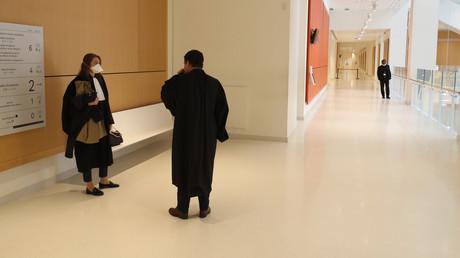 Des avocats portant des masques attendent devant une salle d'audience du nouveau palais de justice de Paris, le 20 avril 2020, au 35e jour d'un confinement en France visant à freiner la propagation de la maladie COVID-19, causée par le nouveau coronavirus.