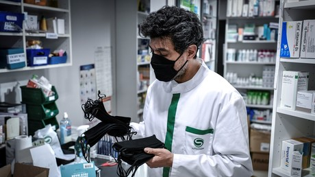 Un pharmacien portant un masque protecteur, montre les masques lavables et en tissu vendus dans une pharmacie à Paris, le 29 avril 2020 (image d'illustration).