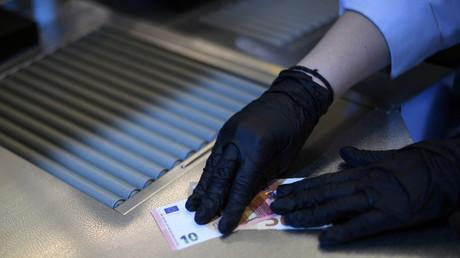 Un billet de 10 euros manipulé avec des gants de protection en pleine pandémie du Covid-19.
