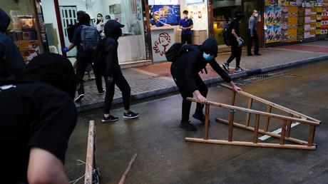 Des manifestants déplacent du mobilier urbain lors d'un rassemblement à Hong Kong, le 10 mai 2020.