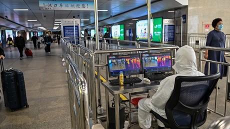 Un technicien contrôle la température des passants dans une gare de Wuhan.