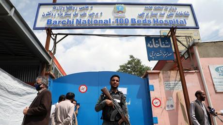 Un policier afghan surveille l'extérieur d'un hôpital qui a été attaqué à Kaboul.