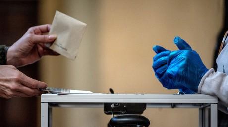 Un électeur dépose son bulletin devant un fonctionnaire équipé de gants en plastique dans un bureau de vote de Lyon, le 15mars 2020, lors du premier tour des élections municipales.
