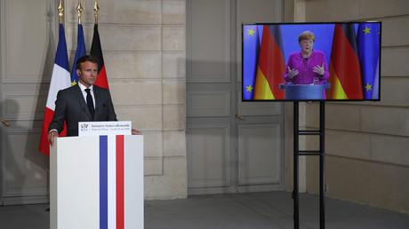 Le président français Emmanuel Macron écoute la chancelière allemande Angela Merkel depuis le palais de l'Elysée à Paris à  l'occasion d'une conférence de presse vidéo conjointe, le 18 mai 2020.