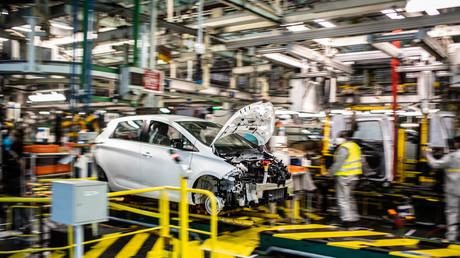 Des employés portant des masques de protection travaillent le long de la chaîne de montage qui produit à la fois le véhicule électrique Renault Zoé et le véhicule hybride Nissan Micra, à Flins-sur-Seine, le plus grand site de production Renault en France le 6 mai 2020.
