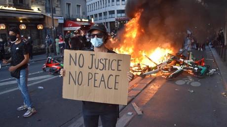 Un manifestant brandit une pancarte «Pas de justice, pas de paix», devant un feu.