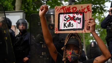 Une manifestante tient une pancarte «The police kills [la police tue]» devant les forces de l'ordre à Marseille, le 6 juin 2020.