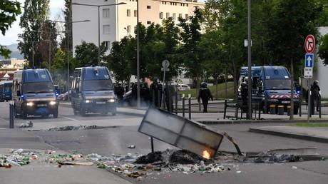 Des gendarmes se tiennent près de leurs véhicules alors que des ordures brûlent dans une rue du quartier des Gresilles à Dijon, le 15 juin 2020.