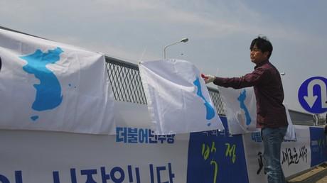 Un homme installe un drapeau en faveur de l'unification de la péninsule coréenne à Paju, Corée du Sud, en avril 2018, en amont d'un sommet inter-coréen (image d'illustration).