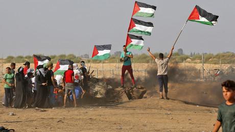 Des manifestants palestiniens brandissent le drapeau national à la suite d'une manifestation frontalière à l'est de Khan Yunis dans le sud de la bande de Gaza le 23 août 2019. (Image d'illustration)