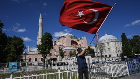 Un homme brandit un drapeau national turc alors que les gens se rassemblent à l'extérieur du musée de Sainte-Sophie le 10 juillet 2020 à Istanbul pour célébrer la révocation du statut de musée, transformant la basilique en mosquée.