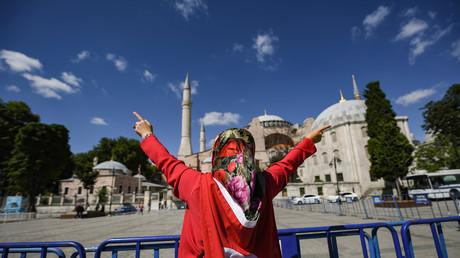 Un femme drapée dans un drapeau turc lève les bras face à Sainte-Sophie pour célébrer la révocation de son statut de musée, transformant la basilique en mosquée, le 10 juillet 2020 à Istanbul.