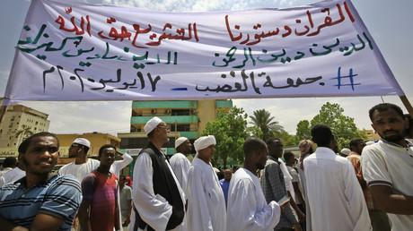 Des manifestants défilent avec une bannière en arabe sur laquelle on peut lire : «Le Coran est notre constitution, la législation est le droit de Dieu», lors d'une manifestation dans le district de Khartoum est, au Soudan, le 17 juillet 2020.
