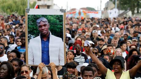 Une personne tient un portrait de feu Adama Traoré lors d'une marche, le 21 juillet 2018 à Beaumont-sur-Oise, au nord-est de Paris (image d'illustration).