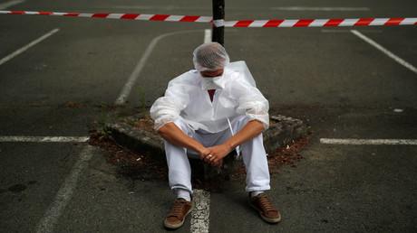 Un soignant, portant une combinaison de protection et un masque, fait une pause, près de l'hôpital de Laval, Mayenne, France