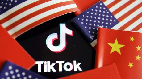 Image d'illustration des drapeaux américain et chinois entourant le logo de l'application TikTok.