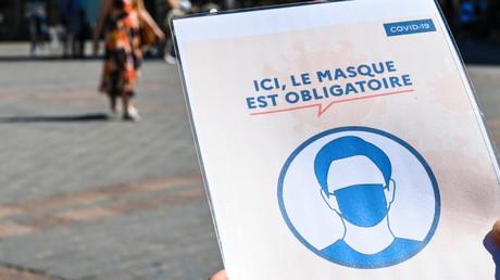 Des personnes portant des masques de protection passent devant un panneau indiquant «Ici, le masque de protection est obligatoire» dans une rue de Lille, le 30 juillet 2020 (image d'illustration).