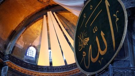 Des rideaux couvrent les fresques chrétiennes de l'ancienne basilique byzantine Sainte-Sophie, reconvertie en mosquée, lors de prières, à Istanbul le 26 juillet 2020.