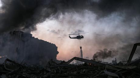 Un hélicoptère éteint un incendie sur les lieux d'une explosion dans le port de Beyrouth, la capitale libanaise, le 4 août 2020.