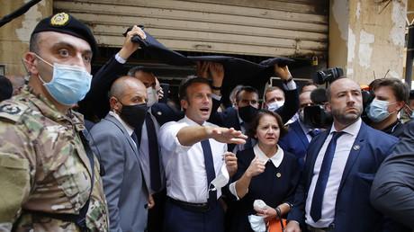Le président de la République française Emmanuel Macron visitant une rue dévastée de Beyrouth le 6 août.