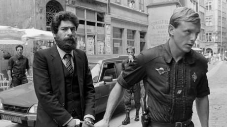Photo d'archive montrant le militant des Factions armées révolutionnaires libanaises (FARL) George Ibrahim Abdallah escorté par un gendarme français à son arrivée au palais de justice de Lyon, le 10 juillet 1986.