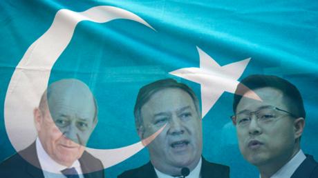 Le ministre français des Affaires étrangères (Jean-Yves Le Drian), le chef de la diplomatie américaine (Mike Pompeo) et le porte-parole du ministère chinois des Affaires étrangères (Zhao Lijian) sur fond de drapeau ouïghour.