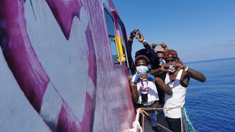 Les premiers migrants secourus en mer par le Louise Michel, à gauche un des graffitis de Banksy.