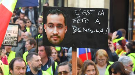 Dans une foule de Gilets jaunes, un manifestant brandit une pancarte représentant Alexandre Benalla, le 16 février 2019 (image d'illustration).