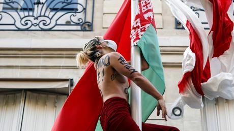 Une activiste du mouvement Femen ajoute au drapeau national biélorusse le drapeau blanc et rouge utilisé par les manifestants biélorusses, au mât se trouvant dans l'enceinte de l'ambassade de Biélorussie à Paris, le 11 septembre 2020.