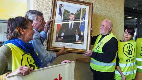 Des militants d'ANV COP21 en train de décrocher un portrait d'Emmanuel Macron à la mairie de Cabestany le 27 février 2019. (Image d'illustration)