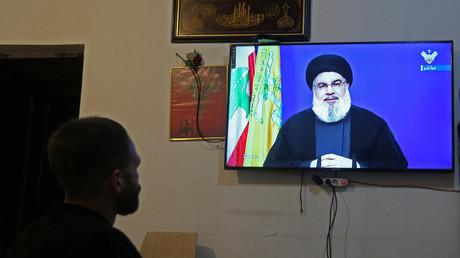 Homme regardant le discours du chef chiite Hassan Nasrallah à la télévision dans une boutique le 29 septembre à Houla au Liban (image d'illustration).
