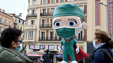 Des personnes portant des masques marchent le 24 septembre 2020 près d'une statue de 6 mètres de haut représentant un «Superhealthworker», installée à Madrid pour rendre hommage aux «héros» qui luttent contre le coronavirus (image d'illustration).