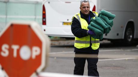 Un fonctionnaire des forces frontalières transporte des couvertures utilisées par des migrants, à Croydon, en Grande-Bretagne, le 23 octobre 2016 (image d'illustration).